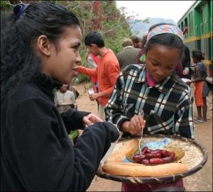 Jeune fille proposant des saucisses maison aux passagers du train.