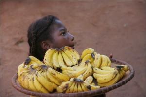 Jeune fille proposant des bananes aux passagers du train.