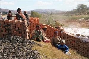 Les briques sont stockées sur le bord de la route en attendant d'être chargées sur les véhicules de livraison. C'est le travail des femmes.