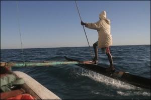 Gilles, en équilibre sur le flotteur, scrute l'horizon pour apercevoir la passe de Mangily.